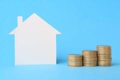 Haus mit Geld auf Blau lizenzfreie stockbilder