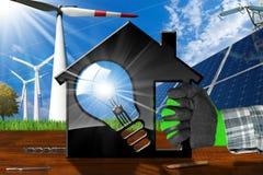 Haus mit Glühlampe und erneuerbaren Ressourcen Lizenzfreies Stockfoto