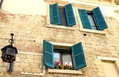 Haus mit offenen Fenstern und Blumen nahe der Kathedrale von Verona Stockbild