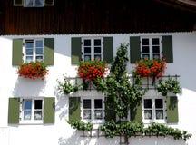 Haus mit sechs Fenstern und roten Blumen in Oberammergau im Bayern (Deutschland) Stockbild