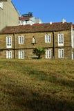 Haus mit Steinziegelsteinen, weißen Fenstern, Dachplatten, Palme und Gras lizenzfreie stockbilder