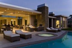 Haus mit Sunloungers auf Patio durch Pool an der Dämmerung Stockbilder