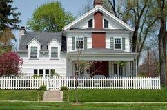 Haus mit weißem Palisadenzaun Stockbild