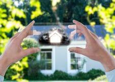 Haus mit Wolke auf futuristischem Gerät vor einem Haus Stockbilder