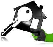 Haus-Modell mit Schlüssel in einer behandschuhten Hand Lizenzfreies Stockfoto