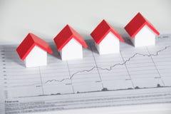 Haus-Modelle auf Finanzdiagramm am Schreibtisch Lizenzfreie Stockbilder