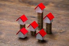 Haus-Modelle auf Staplungsmünzen Stockfoto
