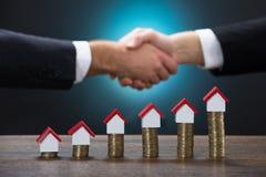 Haus-Modelle auf Staplungsmünzen mit den Geschäftsmännern, die Hände rütteln Lizenzfreies Stockbild