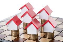 Haus-Modelle und Staplungsmünzen auf Schachbrett Stockfotos