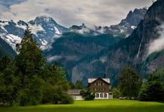 Haus nah an einem steilen felsigen Berg stockfotos