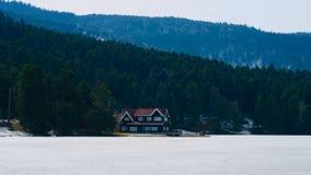 Haus nahe gefrorenem See Stockfotografie