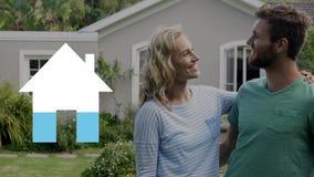 Haus ouside des glücklichen Paars, das die Schlüssel und leere Hausikone ausfüllend Blau hält stock video footage