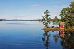 Haus reflektiert im szenischen See Stockfotos