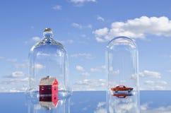 Haus und Auto spielen Symbole in der Glasglocke stockfoto
