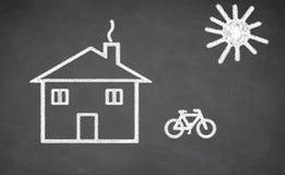 Haus und Fahrrad gezeichnet auf Tafel Lizenzfreies Stockfoto