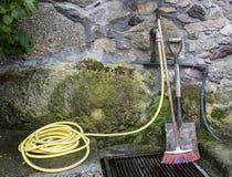 Haus- und Gartenreinigungswerkzeuge mit Wasser bespritzen eine Schaufel und einen Besen mit einem Schlauch Stockfotografie