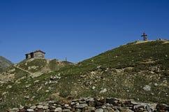 Haus und Kreuz auf den Spitzenbergen in einem touristischen Weg Stockfoto