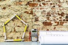 Haus und Projekte auf Backsteinmauerhintergrund stockfotos