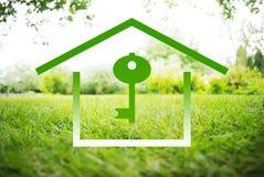 Haus und Schlüssel-Symbole auf einem grünen Sommer gestalten landschaftlich Lizenzfreies Stockfoto