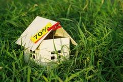Haus vom Papier mit einer leeren gelben Karte mit einer Aufschrift von 70% in einem grünen Gras Lizenzfreie Stockfotos