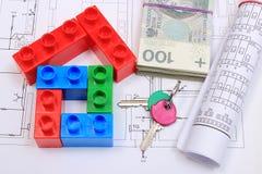 Haus von bunten Bausteinen, von Schlüsseln, von Banknoten und von Zeichnungen Stockfotos