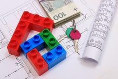 Haus von bunten Bausteinen, von Schlüsseln, von Banknoten und von Zeichnungen Lizenzfreie Stockfotos