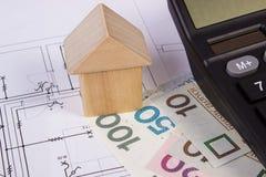 Haus von Holzklötzen und von polnischem Geld mit Taschenrechner auf Bauzeichnung, Gebäudehauskonzept Stockfotos