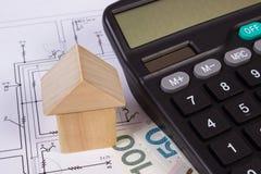 Haus von Holzklötzen und von polnischem Geld mit Taschenrechner auf Bauzeichnung, Gebäudehauskonzept Stockbild