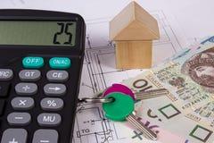 Haus von Holzklötzen und von polnischem Geld mit Taschenrechner auf Bauzeichnung, Gebäudehauskonzept Stockfotografie