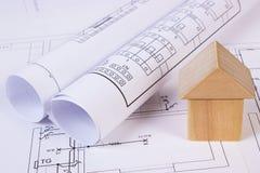 Haus von Holzklötzen und von Rollen von Diagrammen auf Bauzeichnung des Hauses Stockfotos