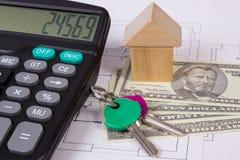 Haus von Holzklötzen und von Währungsdollar mit Taschenrechner auf Bauzeichnung, Gebäudehauskonzept Stockfotos