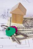 Haus von Holzklötzen, von Schlüsseln und von Währungsdollar auf Bauzeichnung, Gebäudehauskonzept Lizenzfreies Stockfoto