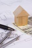 Haus von Holzklötzen, von Währungen Dollar und von Zubehör für das Zeichnen, errichtendes Hauskonzept Lizenzfreies Stockfoto