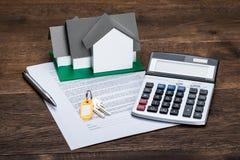 Haus vorbildliches On Contract Paper mit Schlüsseln und Taschenrechner Stockfotografie