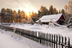 Haus wird durch Schnee im Holz an der Dämmerung umgeben Stockbilder