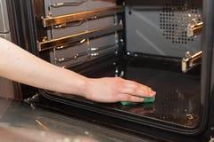 Hausarbeit- und Haushaltungskonzept Schrubben des Ofens und des Ofens Weibliche Hand mit dem grünen Schwamm, der den Küchenofen s lizenzfreies stockbild