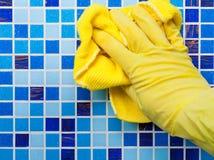 Hausaufgaben - Abwischen der Badezimmerwand mit Putztuch Stockfotos