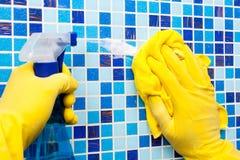 Hausaufgaben - Abwischen der Badezimmerwand mit Putztuch und spr Lizenzfreies Stockfoto