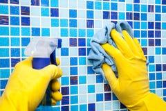 Hausaufgaben - Abwischen der Badezimmerwand mit Putztuch und spr Lizenzfreie Stockfotografie