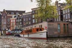 Hausboot mit Schiff auf dem Wasser in Amsterdam Lizenzfreie Stockfotos