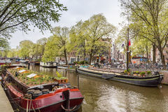 Hausboot und Schiff mit Blumen auf dem Wasser in Amsterdam Lizenzfreie Stockbilder