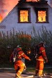 Hausburning und -Feuerwehrmänner Lizenzfreies Stockfoto