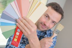 Hausdekorateur, der Farbmuster und Farbenrolle hält Lizenzfreies Stockfoto
