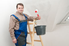 Hause painter. Man on ladder paiting wall by roller Royalty Free Stock Images