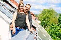 Hauseigentümer sind mit Sonnenkollektoren auf seinem Dach glücklich Stockfotografie