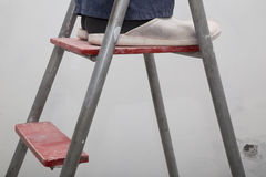 Hauserneuerung Meister in der Uniform auf der Leiter Stockbilder