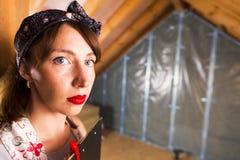 Hausfrau am Dachbodenerneuerungsstandort mit, zum der Liste in ihren Händen zu tun stockfotos