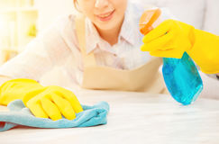 Hausfrau in den gelben Handschuhen, die Tabelle säubern lizenzfreies stockfoto