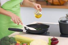 Hausfrau der jungen Frau, die in der Küche beim Addieren des Olivenöls kocht Konzept der neuen und gesunden Mahlzeit zu Hause Lizenzfreie Stockfotografie