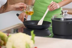 Hausfrau der jungen Frau, die in der Küche beim Addieren des Olivenöls kocht Konzept der neuen und gesunden Mahlzeit zu Hause Lizenzfreies Stockfoto